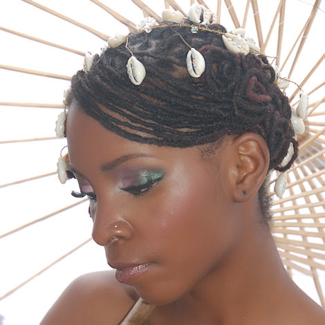 black woman with loced bridal hairstyle and cowrie shells